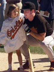 In 1997, Orioles all-star outfielder Brady Anderson poses with then-6-year-old Kelley Deegan before an exhibition game with the Red Wings.