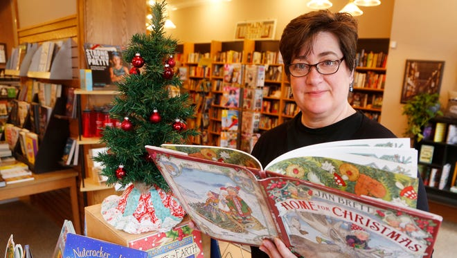 "Owner Tamzin Malone with ""Home for Christmas,"" by Jan Brett Friday, December 15, 2017, at Main Street Books, 426 Main Street in Downtown Lafayette. Main Street Books has a variety of Christmas books for children."