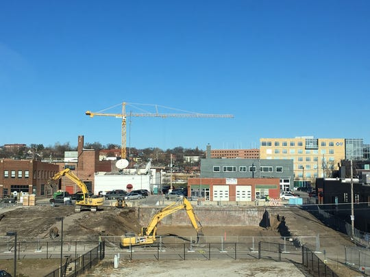 Workers prepare the site at 1400 Walnut St. for the construction of a 90-unit apartment complex.