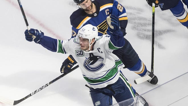Vancouver Canucks' Bo Horvat (53) celebrates his goal as he is followed by St. Louis Blues' Alex Pietrangelo (27) during overtime in an NHL hockey Stanley Cup first-round playoff series on Friday.