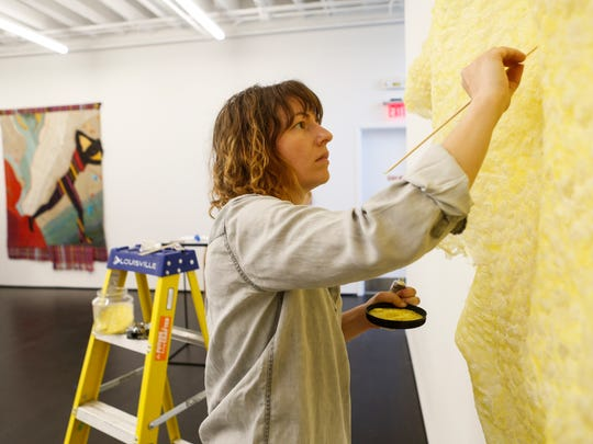 """Artist Sarah Briland puts the finishing touches on her piece """"Phospharus"""" from a series titled Problematica inside at the Kentucky Museum of Art and Craft. The museum will reopen July 1 after undergoing a complete renovation. June 29, 2016"""