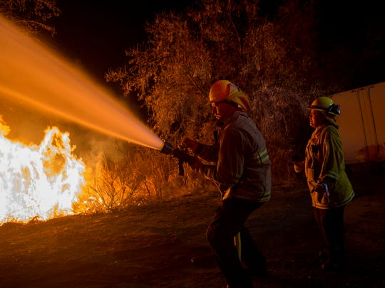 Members of the San Juan County Fire Department contain a back burn Saturday as they battle a wildfire in Bloomfield.