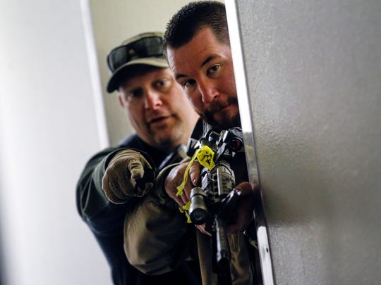 Farmington Police Department Sgt. Nick Bloomfield, left, and Detective Kenneth Smith work together during an active-shooter exercise on Wednesday at a hangar at the Four Corners Regional Airport in Farmington.