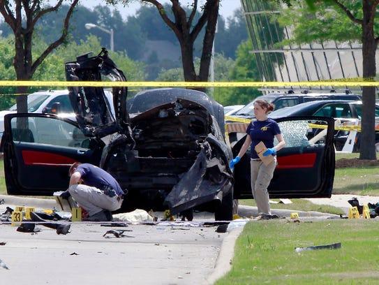 Investigators work a crime scene before the removal