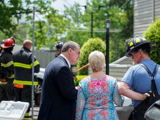 KFD officials converse with a resident following a fire at the Meadow Woods apartment complex on Pleasant Ridge Road on Sunday.