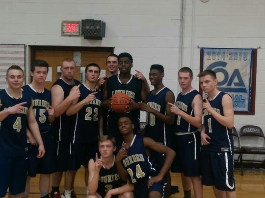 James Anozie poses with his team after scoring his 1,000th point Friday