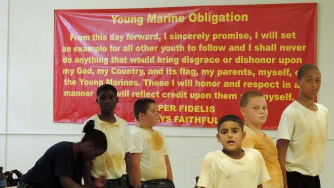 Recruits stand in front of the Young Marines Obligation they will memorize during their recruit training.