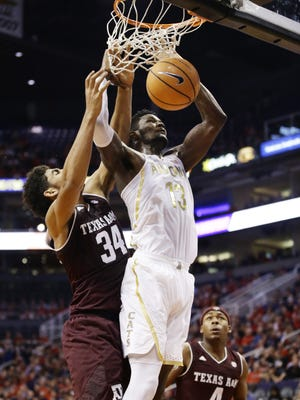 Arizona's Deandre Ayton is fouled by Texas A&M's Tyler Davis in the first half during the Valley Of The Sun Shootout on Dec. 5, 2017 at Taking Stick Resort Arena in Phoenix, Ariz.