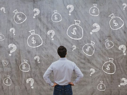 A man facing a chalkboard with his hands on his hips and bags of money and question marks drawn on the chalkboard.