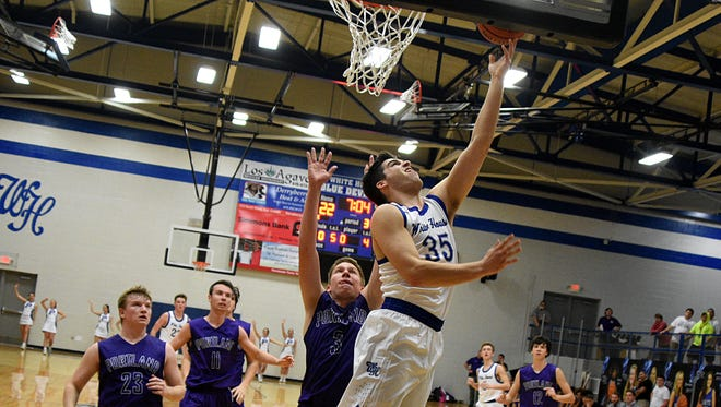 White House senior Zach Baldwin elevates for a layin as Portland junior Luke Jones defends during third-quarter action. Baldwin scored seven points in the Blue Devils' 57-39 victory.