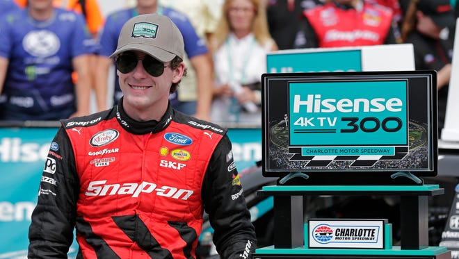 Ryan Blaney poses with the trophy in Victory Lane after winning the NASCAR Xfinity race at Charlotte Motor Speedway.