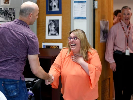 Ozark Junior High School teacher Natalie Houston reacts with excitement and shock after being surprised by her favorite playwright, Don Zolidis, in her class on Wednesday.