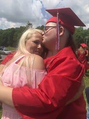 Emily Milam, 18, hugs her mom, Gloria Milam after graduating.