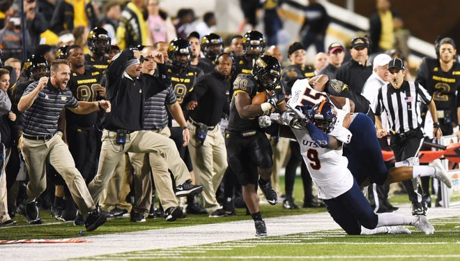 Southern Miss players and coaches along the sideline cheer as running back Jalen Richard breaks free on a run against Texas-San Antonio on Oct. 17 at M.M. Roberts Stadium.