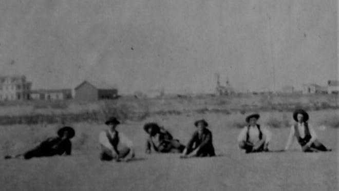 This photo shows six men sitting on the ground with one of them, the man on the far right, identified as J. B. Jones, an early surveyor of Lubbock County. In the near background a shallow gash in the land runs through the tableau. In the far background one can see the large Nicolett Hotel with its two-level porch and several other structures.