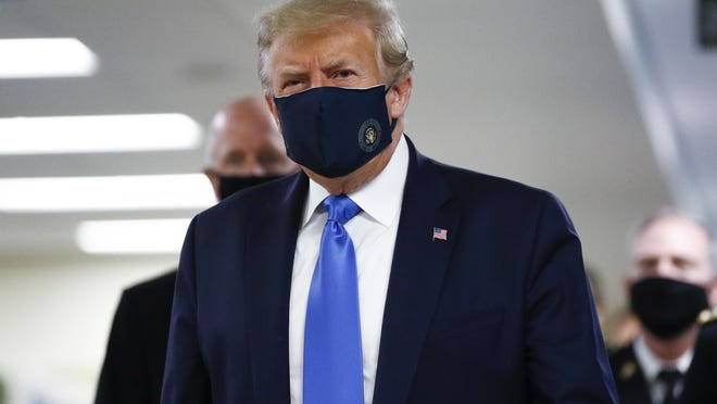 President Donald Trump wears a mask as he walks down the hallway during his visit to Walter Reed National Military Medical Center in Bethesda, Maryland July 11.