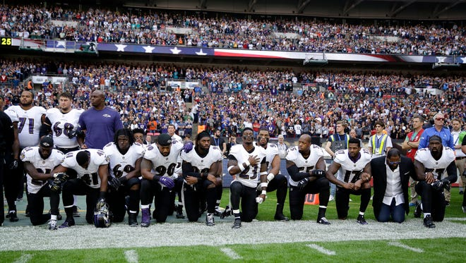 FILE - In this Sunday Sept. 24, 2017 file photo, Baltimore Ravens players, including former player Ray Lewis, second from right, kneel down during the playing of the U.S. national anthem before an NFL football game against the Jacksonville Jaguars at Wembley Stadium in London. Joey Odoms, a combat veteran who has been the Ravens' national anthem singer for the past three years, announced his resignation as debate continues about players kneeling during the national anthem.