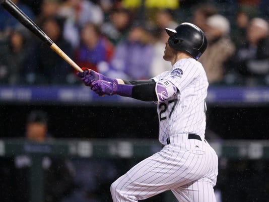 Colorado Rockies' Trevor Story follows the flight of his grand slam off San Francisco Giants starting pitcher Johnny Cueto in the fourth inning of a baseball game Friday, April 21, 2017, in Denver. (AP Photo/David Zalubowski)