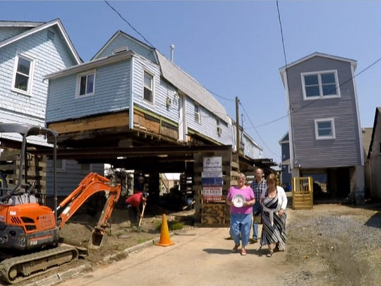 Eileen Scanlon (striped dress) walks with Barbara Hartsgrove outside the 5th Avenue home she is having raised in Highlands Wednesday, May 25, 2016.  During that process a 44-foot wooden boat was exposed from underneath the home being lifted to put it on pilings.