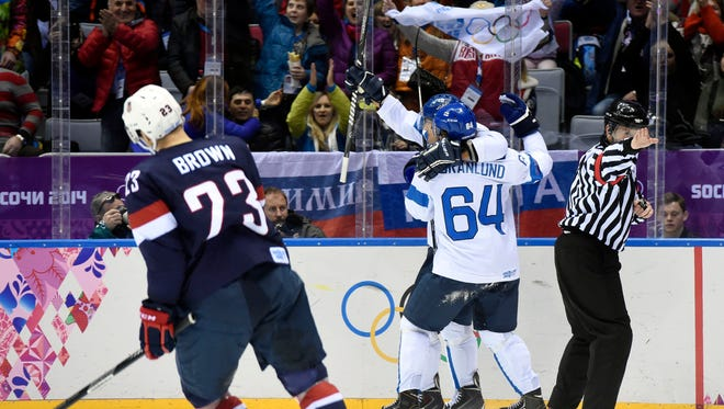 Finland forward Teemu Selanne (8) celebrates his goal with forward Mikael Granlund as the USA's Dustin Brown skates away dejected.