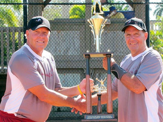 Manager Craig Cunningham of DaVinciâ??s (left) receives the Island Division Championship Trophy from League Commissioner Bill Shurina.