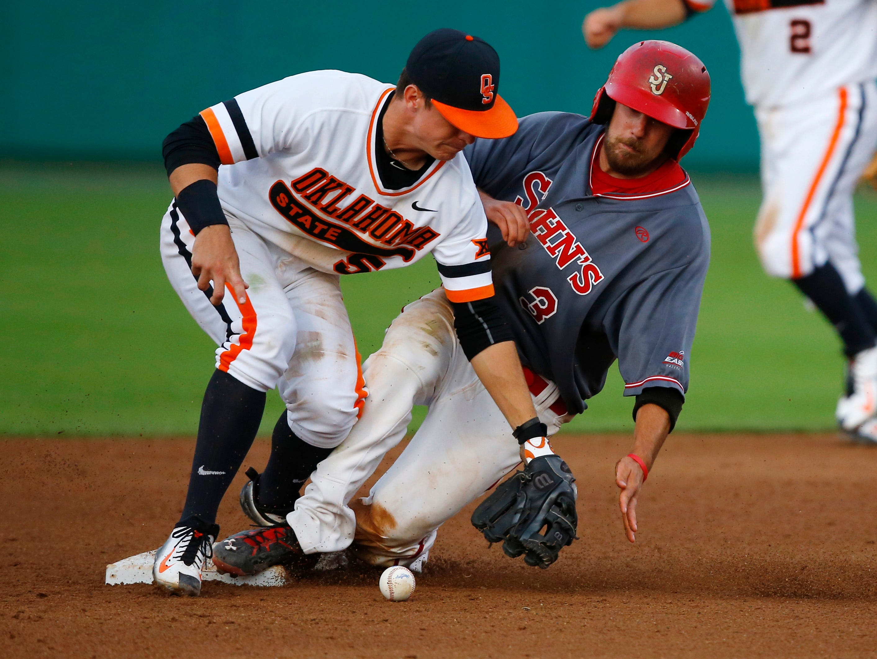 Robert Wayman (3) of St. John's slides safely into second base as Oklahoma State shortstop Donnie Walton (5) takes the throw during their regional game in Stillwater, Okla., on Sunday.