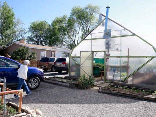 Customers Lockey Caston and Inez Caston of Kirtland walk into the Brewer Greenhouse on Thursday in Farmington.