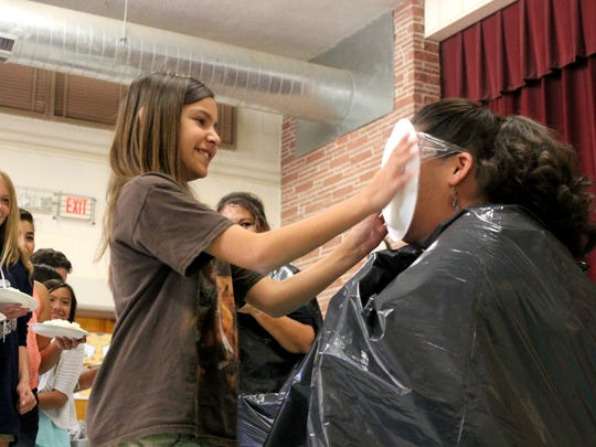 Tiana Solorio, fifth grader, smacks teacher Melinda Fisk in the face with whipped cream.