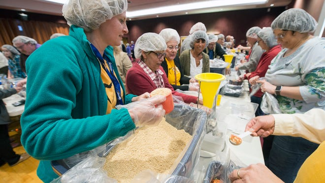 Erika Juran, of the Unitarian Universalist Congregation of York, left, packs a meal. Temple Beth Israel, Luther Memorial Church, St. Paul's Lutheran Church, and the Unitarian Universalist Congregation of York gather at Temple Beth Israel, in York Township Sunday March 13, 2016 to combine over 10,000 dry meals.