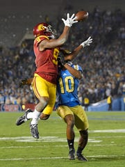 Southern California wide receiver JuJu Smith-Schuster, left, makes a catch as UCLA defensive back Fabian Moreau defends during the first half of an NCAA college football game Saturday, Nov. 19, 2016, in Pasadena, Calif. (AP Photo/Mark J. Terrill)