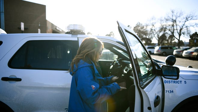 In a Dec. 21, 2017 photo, Samantha Rabins, of Mental Health Center of Denver, prepares to roll out with an officer at Denver Police District 5 in Denver.  Faced with escalating arrests in Colorado, the state is prodding police departments to try new diversion programs for those with mental illnesses or drug addictions. Instead of just arresting troubled individuals, police in Boulder and Denver now are having mental health clinicians ride along when police respond to emergency 911 calls. (Aaron Ontiveroz//The Denver Post via AP)