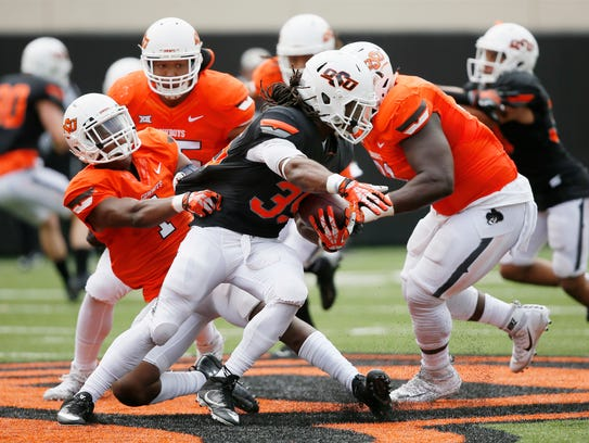 Oklahoma State running back Jakeem Johnson, is tackled