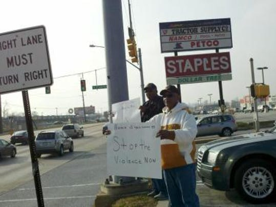 Jerome Carter, 72, and his brother, Bennie Carter, 76, stand along Route 30 in York Saturday holding signs that urge drivers to honk if they want to stop the violence. (Daily Record/Sunday News -- Kara Eberle)