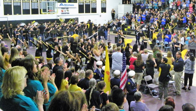 Alamogordo High School band and cheerleading squad lead the Alamogordo Public Schools faculty and staff in a the AHS fight song at the APS General Assembly Monday morning.
