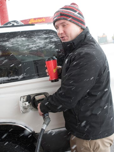 Colton Nelson winces from blowing snow as he refillls