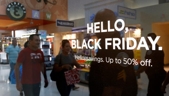 Shoppers walk by signage advertising Black Friday sales at Dolphins Mall in Doral, Fla., on Nov. 24, 2016.