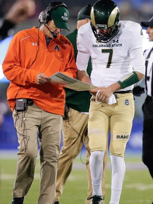 CSU coach Mike Bobo and quarterback Nick Stevens go over the play chart during a timeout in a game last season at Air Force. Bobo and his players realize they have a lot more pressure on them this season than most, as they open a new on-campus stadium and play an ambitious nonconference schedule.