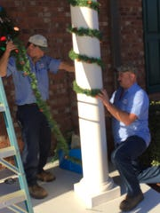 Rick Russell, left, and Chris Schwartz adjust holiday