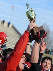 Riverheads head football coach Robert Casto holds up the championship trophy as he presents it to his team for winning the Group A, Division I  championship in 2010.
