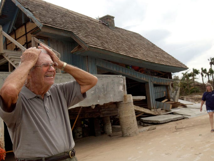 2004: Harold Jefferson, 89, of Vero Beach reacts to the damage done to a neighbor's house while touring the neighborhood on his first day back home.