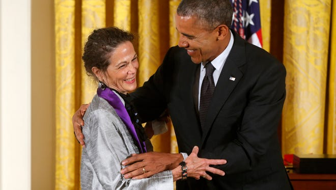 President Barack Obama awards the 2013 National Medal of Arts to Julia Alvarez, a novelist, poet and essayist from Weybridge, during a ceremony Monday in the East Room at the White House in Washington.