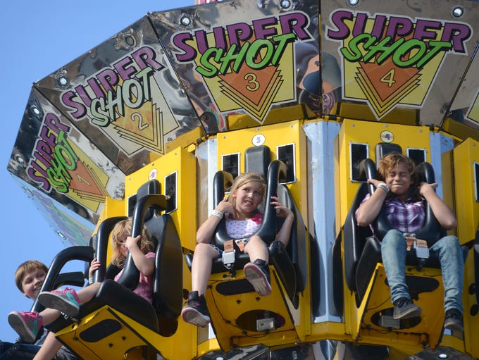 Festival goers enjoy an amusement park ride Saturday