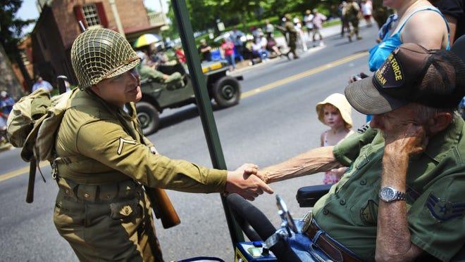 World War II re-enactor Rod Pellegrini stops to shake the hand of Vietnam Air Force veteran Bill Claik on Baltimore Street during the Gettysburg Veterans Memorial Day Parade.