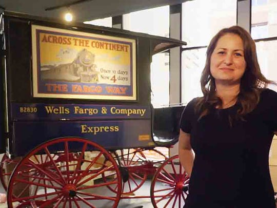 "Megan Schaack, a senior museum manager at Wells Fargo, with the ""Wells Fargo wagon"" in Des Moines."
