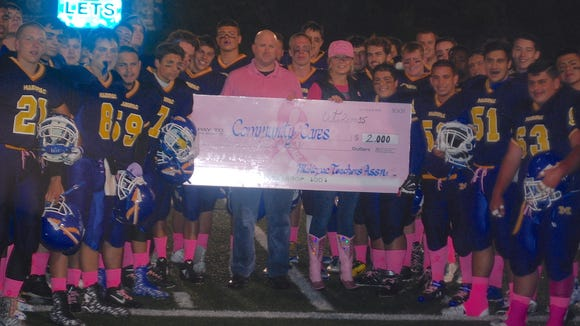 """The Mahopac football team poses with a check that the school donated to Community Cares, a local non-profit, after its second annual """"Pink Game"""" on Oct. 2, 2015."""