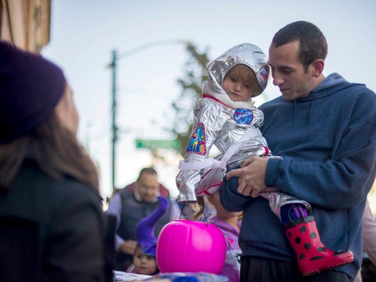 Charlie Huey, 24, of Rochester holds Karolina Huey, 2, while trick or treating on Main St. of Rochester during the tick or treat festivities on Oct. 22, 2016.