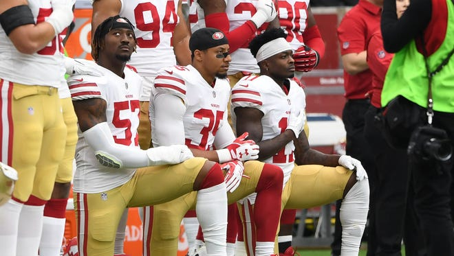 49ers outside linebacker Eli Harold (57), strong safety Eric Reid (35), and wide receiver Marquise Goodwin (11) kneel for the national anthem prior to a game against the Texans.