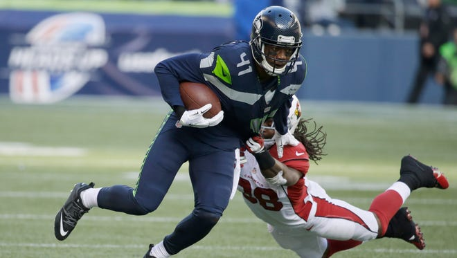 Seattle Seahawks cornerback Byron Maxwell runs the ball after making an interception as Arizona Cardinals running back Andre Ellington, right, attempts the tackle in the first half of an NFL football game in Seattle. NFL free agency begins Tuesday, March 10, 2015.