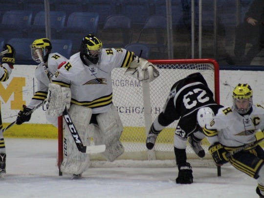 Hartland goalie Brett Tome sidesteps Nathan Nickelson of Grand Rapids Forest Hills Northern/Eastern, who knocked the goal off its moorings after charging the net.