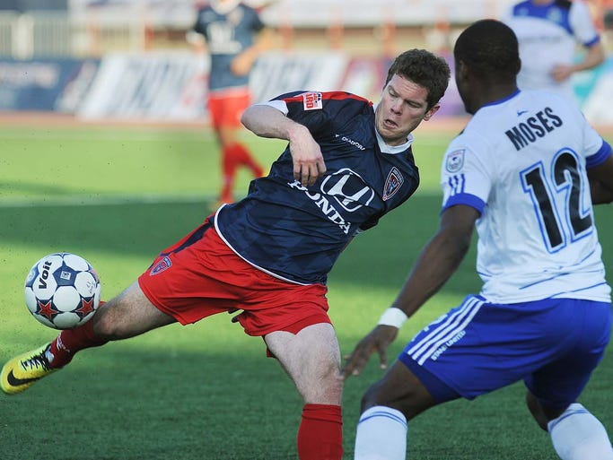 Mike Ambersley of Indy tries to get off a shot in front of the goal as he is defended by Edmonton's Kareem Moses in the first half. The Indy Eleven hosted Edmonton in a NASL soccer match at Michael A. Carroll Stadium Saturday May 10, 2014.